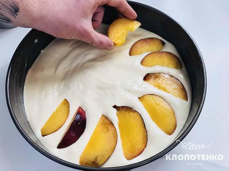 Выложите дольки персика на тесто