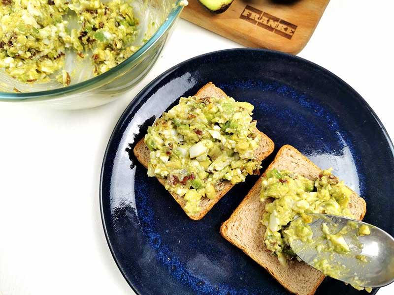 Намажьте подсушенный хлеб пастой из авокадо