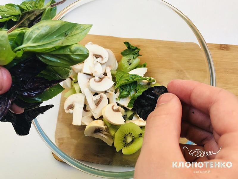 Листики базилика добавьте в миску с грибами и киви