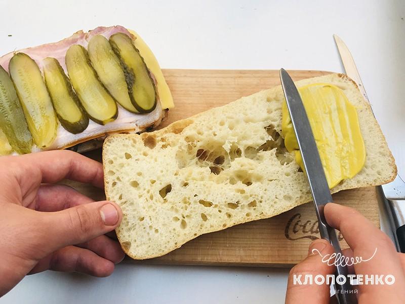 Выложите слой огурцов и намажьте горчицей верхнюю булочку