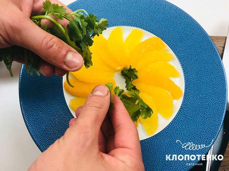 На апельсин выложите промытые листики кинзы