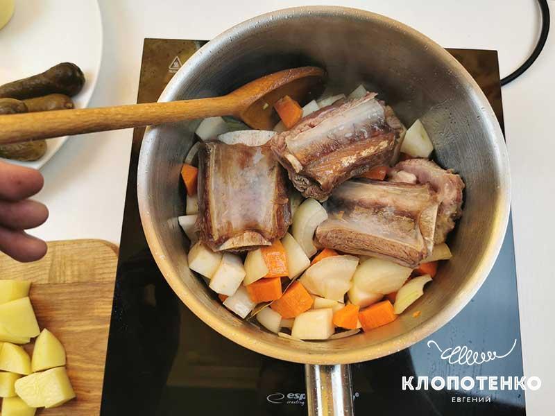 Добавьте нарезанные овощи в кастрюлю к мясу