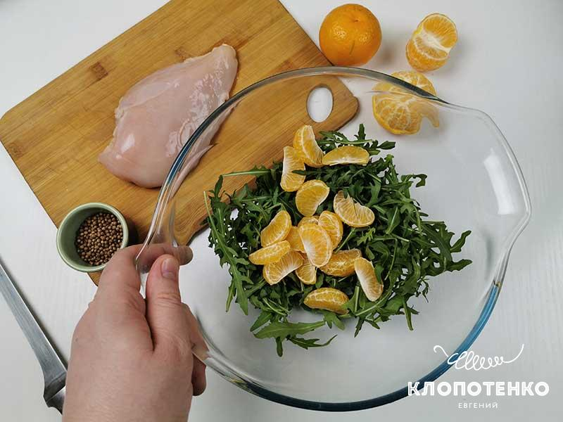 Выложите рукколу и мандарин в салатник