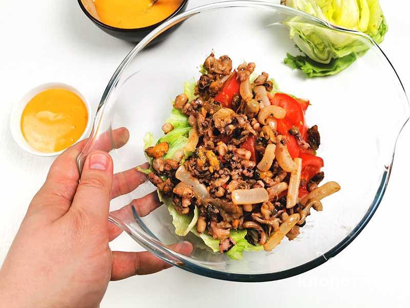 Нарежьте томат и добавьте морепродуктами в миску