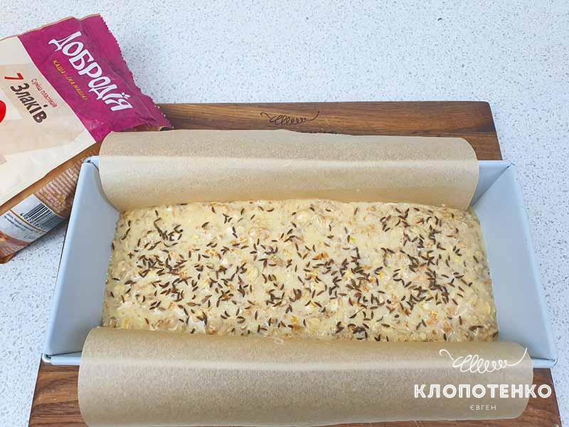Равномерно распределите тесто и посыпьте оставшимися зернами тмина