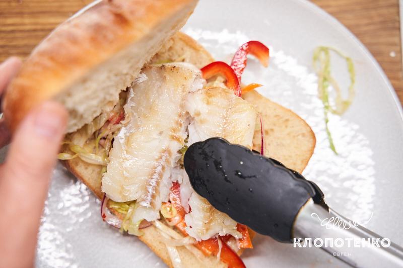 Выложите салат и рыбу в булочку