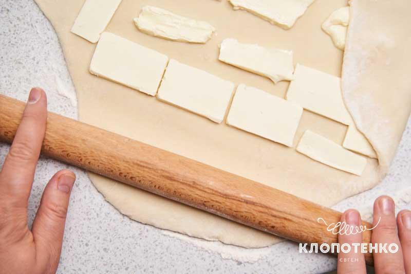 Разложите нарезанные кусочки сливочного масла на раскатанное тесто