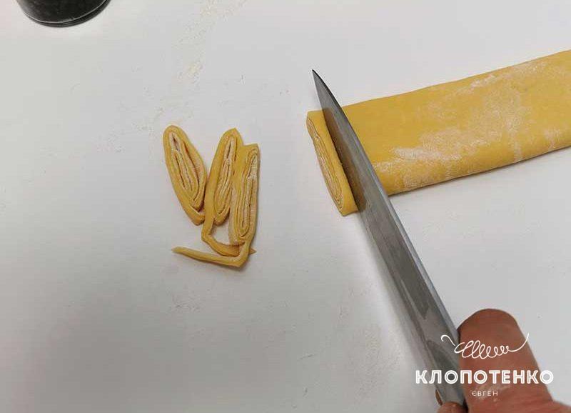 Нарежьте рулет из теста тоненькими полосками